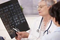 Doctor y paciente que discuten resultados de exploración. Imágenes de archivo libres de regalías
