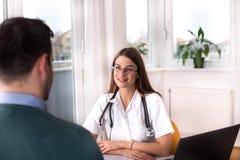 Doctor y paciente que hablan en el escritorio imagen de archivo libre de regalías