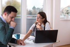 Doctor y paciente que hablan en la tabla fotografía de archivo libre de regalías