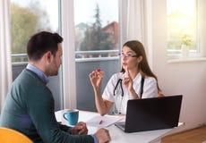 Doctor y paciente que hablan en la tabla fotos de archivo libres de regalías