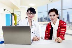 Doctor y paciente que miran la cámara Fotografía de archivo
