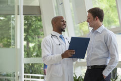 Doctor y paciente que sonríen y que discuten el informe médico en el hospital Imagen de archivo