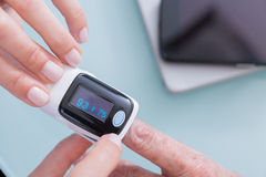 Doctor y paciente que usa el oxímetro del pulso del finger imagen de archivo