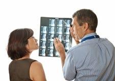 Doctor y paciente que ven exploraciones espinales de MRI Fotos de archivo libres de regalías