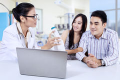 Doctor with young couple in clinic Stock Photo