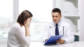 Doctor and young woman meeting at hospital. Medicine, health care and people concept - doctor with clipboard and young woman meeting at hospital stock footage