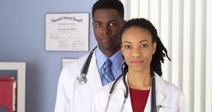 Doctores afroamericanos que se colocan en oficina del hospital fotografía de archivo libre de regalías