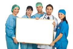Doctores alegres con la bandera en blanco Foto de archivo
