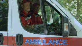 Doctores amistosos en la ambulancia que mira la cámara, servicio de emergencia profesional almacen de video