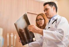 Doctores asiáticos que examinan la película de radiografía de un paciente Fotos de archivo