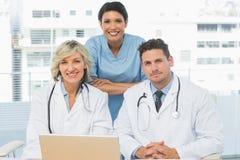Doctores con el ordenador portátil en la oficina médica Fotografía de archivo libre de regalías