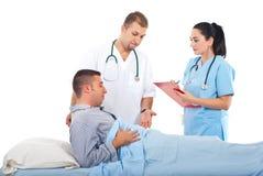 Doctores con el paciente masculino en hospital Fotografía de archivo