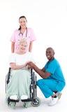Doctores con un paciente en una sonrisa de la silla de rueda Fotos de archivo