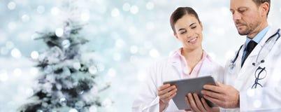 Doctores de la Navidad con la tableta digital en luces borrosas imágenes de archivo libres de regalías