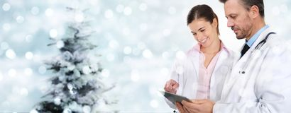 Doctores de la Navidad con la tableta digital en luces borrosas con el tre foto de archivo libre de regalías