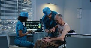 Doctores de sexo femenino que colocan los cables de ECG en paciente almacen de video