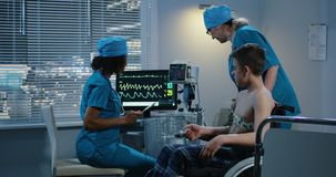 Doctores de sexo femenino que examinan a un muchacho almacen de metraje de vídeo