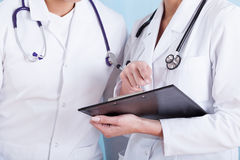 Doctores en delantal blanco médico con los estetoscopios y el tablero imagen de archivo libre de regalías