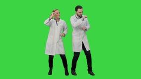 Doctores jovenes en un buen baile y las canciones en una pantalla verde, llave del humor del canto de la croma almacen de video