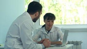 Doctores jovenes que trabajan con un ordenador portátil en una oficina imágenes de archivo libres de regalías