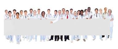 Doctores multiétnicos que sostienen la bandera en blanco Fotos de archivo libres de regalías