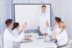 Doctores que aplauden para el colega después de la presentación en hospital Foto de archivo libre de regalías