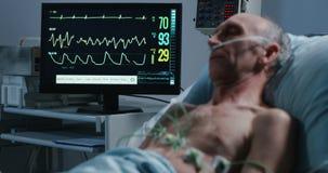 Doctores que colocan los cables en paciente para comprobar ritmo cardíaco metrajes