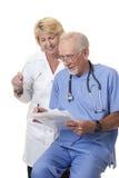 Doctores que discuten las notas del paciente Foto de archivo libre de regalías