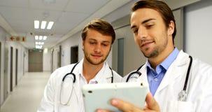 Doctores que discuten sobre la tableta digital en pasillo almacen de metraje de vídeo