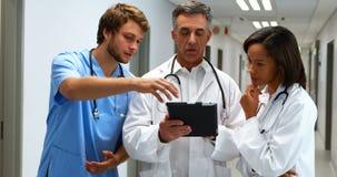 Doctores que discuten sobre la tableta digital en pasillo metrajes