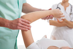 Doctores que examinan el brazo herido Imagen de archivo