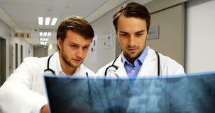 Doctores que examinan informe de la radiografía en pasillo almacen de metraje de vídeo