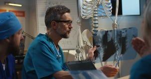 Doctores que examinan la radiografía cervical de la espina dorsal almacen de metraje de vídeo