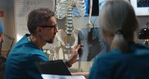 Doctores que examinan la radiograf?a cervical de la espina dorsal almacen de video