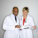 Doctores que leen papeleo. Fotos de archivo