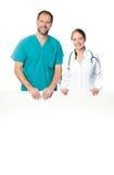 Doctores que llevan a cabo a la tarjeta en blanco Imagenes de archivo