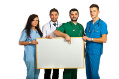 Doctores que llevan a cabo a la tarjeta en blanco Imágenes de archivo libres de regalías