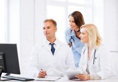 Doctores que miran el ordenador en la reunión fotos de archivo