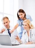 Doctores que miran el ordenador portátil en la reunión Fotografía de archivo libre de regalías
