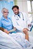 Doctores que muestran informe médico al paciente mayor Imagen de archivo