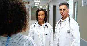 Doctores que obran recíprocamente con la mujer embarazada en pasillo almacen de video