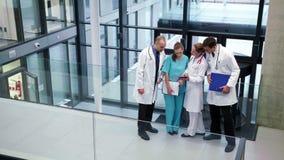 Doctores que obran recíprocamente con uno a en pasillo almacen de metraje de vídeo