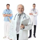 Doctores que se colocan en el fondo blanco, retrato Foto de archivo libre de regalías