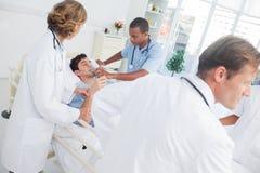Doctores que toman cuidado de un paciente enfermo Fotos de archivo libres de regalías