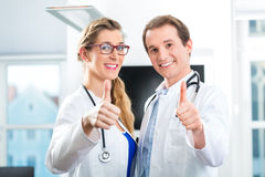 Doctores - varón y hembra, colocándose con un estetoscopio Foto de archivo