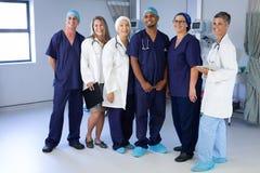 Doctores y cirujanos que se colocan en una clínica fotos de archivo