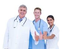 Doctores y enfermera que gesticulan los pulgares para arriba Fotografía de archivo