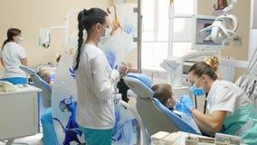 Doctores y pacientes profesionales en oficina dental grande con el equipo moderno almacen de metraje de vídeo