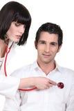Doctorlistening femelle attrayant au battement de coeur de son patient masculin Images libres de droits