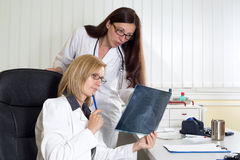 Doctors Analyzing X-ray of Patient Suffering From Lung Cancer in Hospital. Female Doctors Analyzing X-ray of Patient Suffering From Lung Cancer in Hospital stock photography